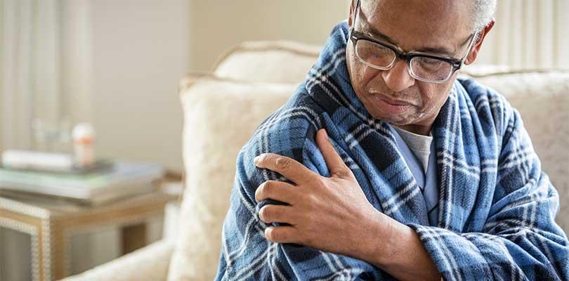 A man sitting in a blue bathrobe, holding his shoulder.